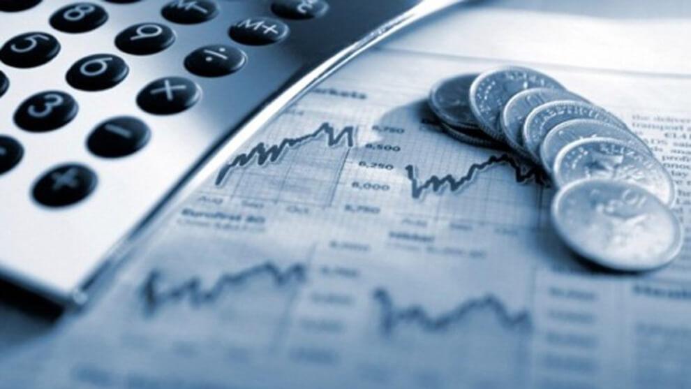 imagen de estadísticas de la economía, encima una calculadora y monedas