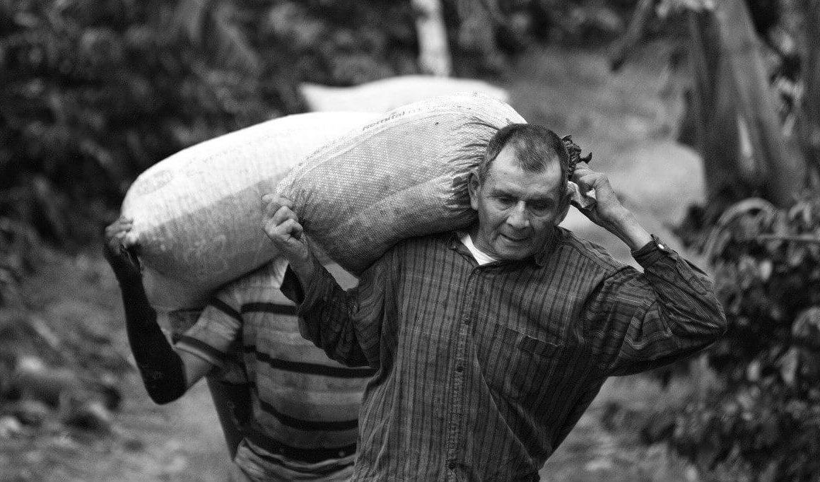 Fotografía tomada en blanco y negro, de un señor cargando un bulto de papa