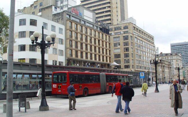 Fotografía del centro de Bogotá en donde se ve el Transmilenio y personas caminando