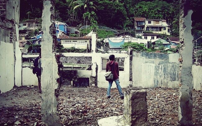 persona en medio de las ruinas de una casa