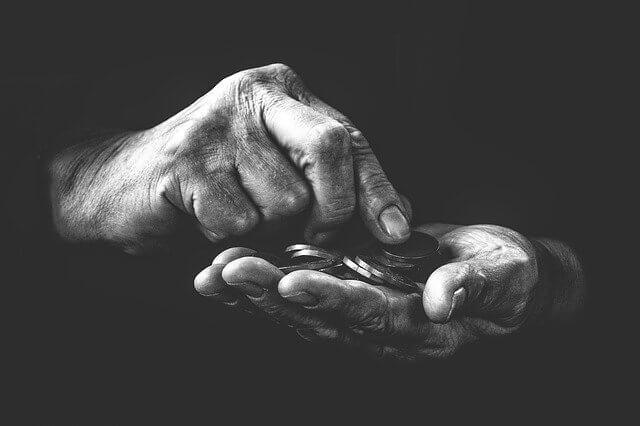 fotografía blanco y negro de unas manos con unas monedas