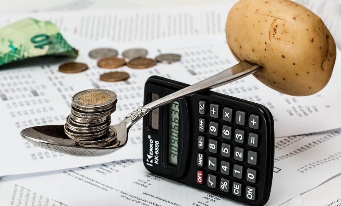 calculadora, monedas, cuchara y papa